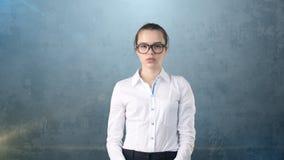 Портрет бизнес-леди в белой юбке на изолированной предпосылке смотря прямо с стеклами запрета волос, оранжевых и черных Стоковое Изображение RF