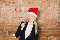 Портрет бизнес-леди красоты с носить шляпы lolipop и santa Предпосылка красного цвета кирпича Стоковые Фотографии RF