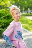 Портрет блондинкы в розовой одежде в парке outdoors Стоковые Фото