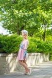 Портрет блондинкы в розовой одежде в парке outdoors Стоковое Изображение RF