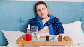 Портрет больной женщины при грипп и лихорадка лежа в кровати с подносом полным пилюлек и медицин стоковое фото rf