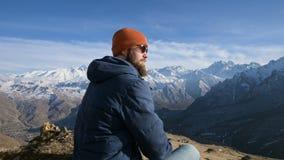 Портрет бородатого путешественника в солнечных очках и крышке сидит на утесе против фона гор сток-видео