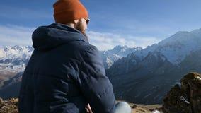 Портрет бородатого путешественника в солнечных очках и крышке сидит на утесе против фона гор акции видеоматериалы