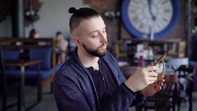 Портрет бородатого битника в стильных eyeglasses сидя в ресторане и смотря камеру Красивый человек на акции видеоматериалы