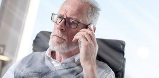 Портрет бородатого старшего бизнесмена говоря на мобильном телефоне, световом эффекте Стоковое Изображение RF