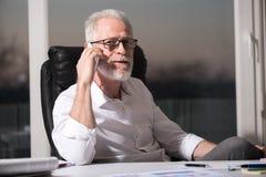 Портрет бородатого старшего бизнесмена говоря на мобильном телефоне, трудном свете Стоковые Изображения RF