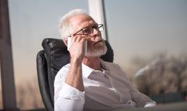 Портрет бородатого старшего бизнесмена говоря на мобильном телефоне, трудном свете Стоковые Изображения
