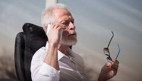 Портрет бородатого старшего бизнесмена говоря на мобильном телефоне, световом эффекте, трудном свете Стоковое Изображение RF