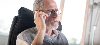 Портрет бородатого старшего бизнесмена говоря на мобильном телефоне, трудном свете Стоковая Фотография RF