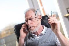 Портрет бородатого старшего бизнесмена говоря на мобильном телефоне, трудном свете Стоковые Фотографии RF
