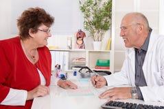 Портрет более старого доктора разговаривая с женским пациентом Стоковое фото RF
