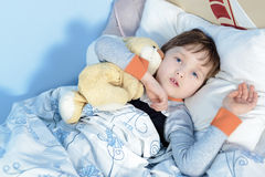 Портрет больного мальчика обнимая плюшевый медвежонка Стоковые Изображения RF