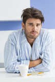 Портрет больного человека с кружкой кофе и склонности медицины на счетчике кухни стоковое фото