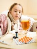 Портрет больной девушки лежа в кровати и смотря чашку чаю Стоковые Фото