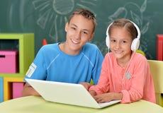 Портрет брата и сестры используя ноутбук стоковая фотография