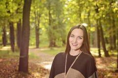 Портрет брюнет молодой женщины в плащпалате шерстей стоя на тропе в зеленом парке на заднем плане в лучах  Стоковая Фотография RF