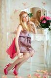 Портрет блестящей белокурой девушки в розовом платье, сидя на th стоковая фотография