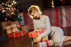 Портрет блестящей белокурой девушки с подарками в руках на bac стоковое фото