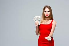 Портрет блестящей молодой женщины в красном платье с ярким составом, красных губах, ожерелье золота Владения женщины в руках a Стоковые Фотографии RF