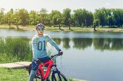 Портрет велосипедиста нося шлем около реки Стоковая Фотография