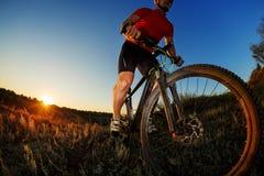 Портрет велосипедиста стоя с горным велосипедом на следе на заходе солнца Стоковое Изображение RF