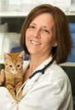 Портрет ветеринара держа котенка в ее клинике стоковое фото