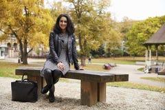 Портрет великобританской мусульманской женщины сидя на стенде в парке Стоковое фото RF