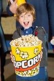 Портрет ведра попкорна excited мальчика предлагая на Стоковые Изображения