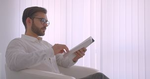 Портрет взгляда со стороны крупного плана взрослого красивого бородатого кавказского бизнесмена в стеклах читая книгу сидя в акции видеоматериалы