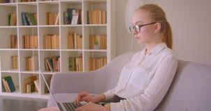 Портрет взгляда со стороны крупного плана молодой милой кавказской белокурой коммерсантки в стеклах используя ноутбук смотря каме видеоматериал