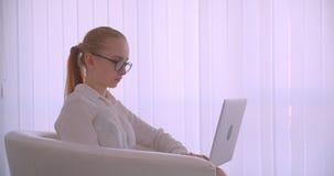 Портрет взгляда со стороны крупного плана молодой милой кавказской белокурой коммерсантки в стеклах используя ноутбук усмехаясь ж сток-видео