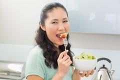 Портрет взгляда со стороны женщины есть салат в кухне Стоковое Фото