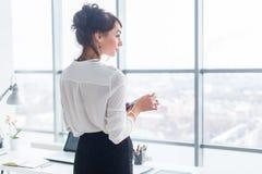 Портрет взгляда со стороны конца-вверх работника отправляя СМС, посылая и читая сообщения во время ее пролома на рабочем месте стоковые изображения rf