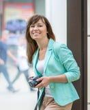 Портрет взрослого счастливого милого усмехаясь кавказского фотографа женщины стоя рядом с стеной на улице города держа фото Стоковая Фотография