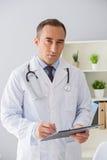 Портрет взрослого доктора стоя на офисе Стоковая Фотография RF