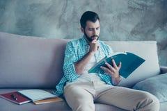 Портрет вид спереди серьезного человека с щетинкой, смотря в книге стоковые изображения rf