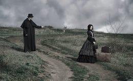 Портрет викторианской дамы в черном усаживании на дороге с ее багажом и джентльменом стоя рядом стоковые изображения rf