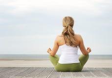 Портрет вид сзади молодой женщины сидя на пляже в представлении йоги Стоковые Фото