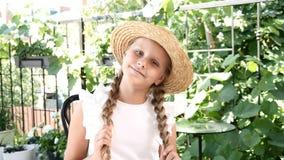 Портрет внушительной маленькой девочки наслаждаясь солнечным днем в парке города держа кабели волос с обеими руками потеха отца р сток-видео