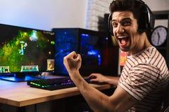 Портрет восторженного парня gamer в наушниках кричащих и rejoi стоковое изображение