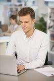 Портрет вскользь бизнесмена работая на компьютере в офисе Стоковые Фото