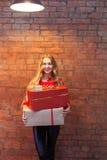Портрет вскользь молодой счастливой усмехаясь подарочной коробки владением женщины снова Стоковое Фото
