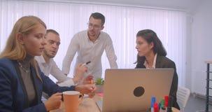 Портрет встречи 4 collleagues в офисе внутри помещения Бизнесмены используя ноутбук и имеющ разговор видеоматериал