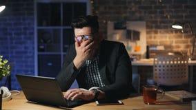 Портрет вымотанной работы предпринимателя зевая с ноутбуком в темном офисе акции видеоматериалы