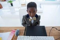 Портрет высокого угла мальчика имитируя как бизнесмен сидя на столе Стоковые Фотографии RF