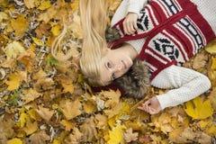 Портрет высокого угла молодой женщины лежа на листьях осени в парке Стоковое Изображение RF