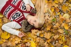 Портрет высокого угла молодой женщины лежа на листьях осени в парке Стоковые Фото