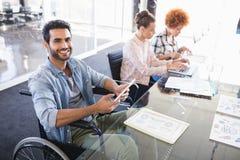 Портрет высокого угла усмехаясь бизнесмена используя цифровую таблетку пока сидящ на кресло-коляске Стоковые Фотографии RF
