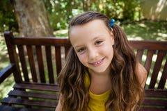 Портрет высокого угла усмехаясь девушки сидя на деревянной скамье Стоковые Фотографии RF
