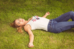 Портрет высокого угла усмехаясь женщины лежа на траве Стоковое Фото